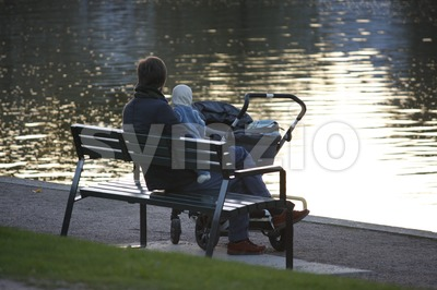 Young Parent Sitting on a Bench with a Baby Stock Photo