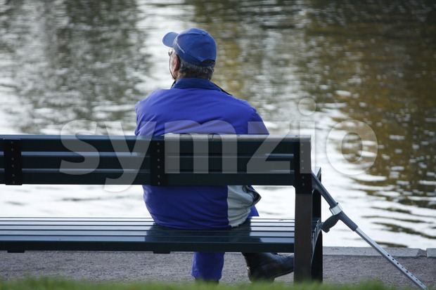 Elderly Man Sitting on a Bench Stock Photo