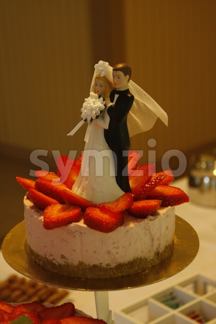 Delicious wedding cake with strawberries and couple on top